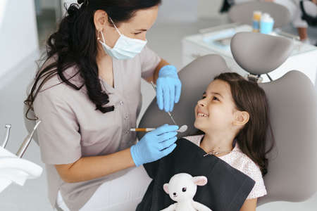 Cute little girl sitting on a modern dental chair and having dental consultation with dentist 스톡 콘텐츠 - 154755533