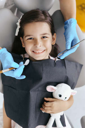 Cute little girl sitting on a modern dental chair and having dental consultation with dentist