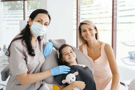 Cute little girl sitting on a modern dental chair with mom and having dental consultation with dentist