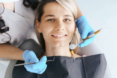 Smiling young woman sitting in dentist chair while doctor examining her teeth. Patient looking at camera 스톡 콘텐츠 - 154755540
