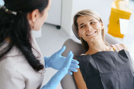 Female Dentist examine and discussing with happy patient about treatment