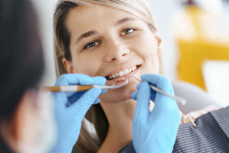 Smiling young woman sitting in dentist chair while doctor examining her teeth 스톡 콘텐츠 - 154755550