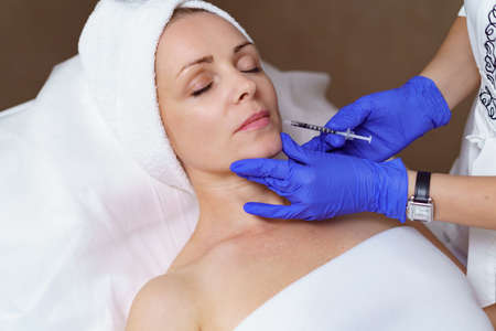 The doctor cosmetologist makes the Rejuvenating facial injections procedure for tightening and smoothing wrinkles on the face skin of a adult woman in a beauty salon