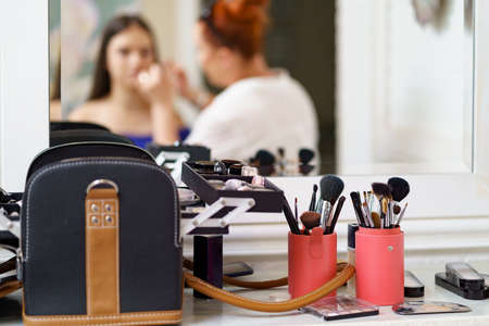 Professional makeup artist working with client in dressing room, reflection in the mirror