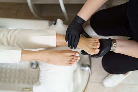 Specialist in beauty salon making french pedicure for female client. Relaxing at beauty salon, caring about nails. Archivio Fotografico