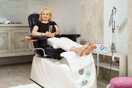 Adult beautiful blond woman enjoying a glass of sparkling whine while relaxing in a leather armchair doing pedicure