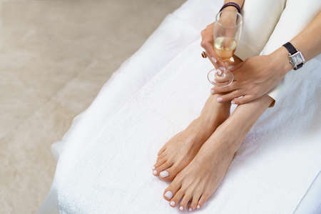 Manicure pedicure with glass with sparkling wine close up on white perfect shape hands spa salon
