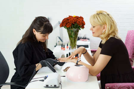 Woman manicurist wearing black gloves making manicure in luxury beauty salon with modern equipment, soft colors, nail service, perfect client hands.