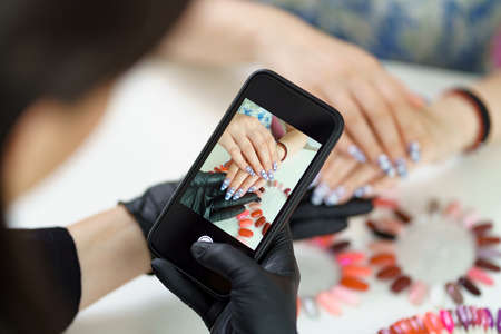 Manicurist takes a photograph of her work, beautiful woman manicure, with a smartphone Archivio Fotografico