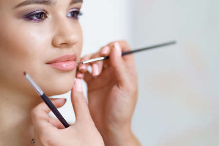 Professional makeup artist working with client in dressing room applying lipstick with a brush Archivio Fotografico