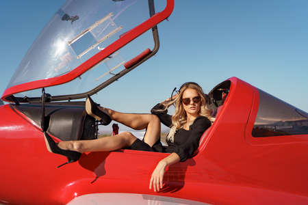 Fashionable women in black dress with beautiful legs wearing black high hills shoes posing in a red aircraft on sky background