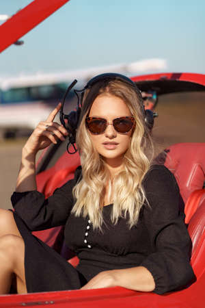 Young fashionable woman pilot in headset ready to fly in small red airplane. Beautiful life, aristocratic lady in black dress in blonde wavy hair.