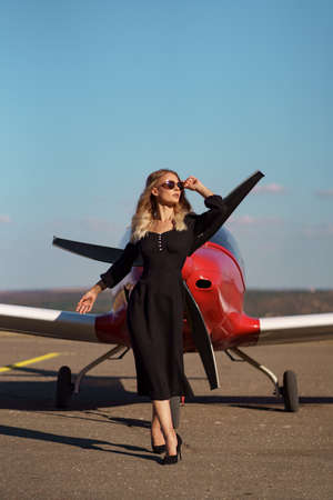 Fashionable women in beautiful classy black dress and beautiful sunglasses posing on a red private plane and blue sky in background