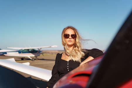 Beautiful blonde woman wearing modern sunglasses posing near a red private plane with sky in background Archivio Fotografico