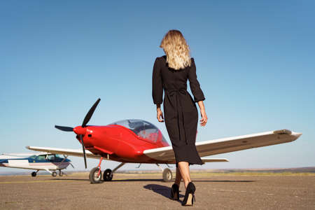Back view Fashionable women in beautiful classy black dress walking to a red private plane and blue sky in background