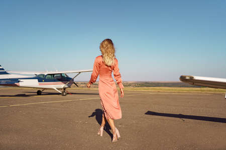 Back view Fashionable women in beautiful classy pink dress walking to a private plane and blue sky in background Archivio Fotografico