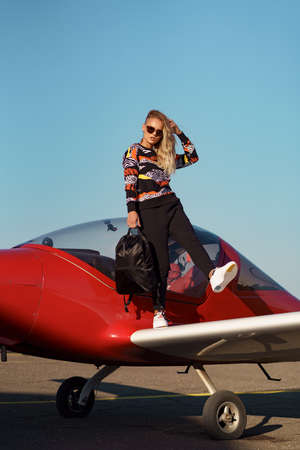 Carefree woman model with a modern haircut and fashionable sunglasses posing near a red plane wearing trendy casual outfit and black backpack