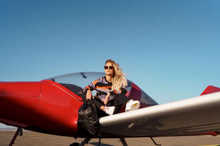 Young woman model with a modern haircut and fashionable sunglasses posing near a red plane wearing trendy casual outfit and black backpack