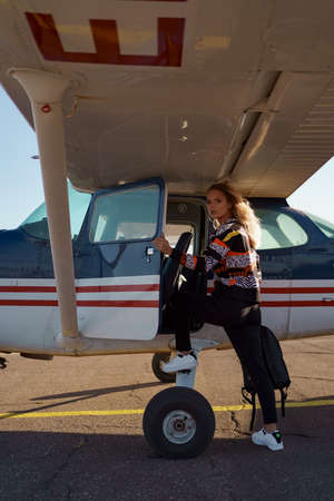 Young woman model with a modern haircut posing near a private plane wearing trendy casual outfit and black backpack