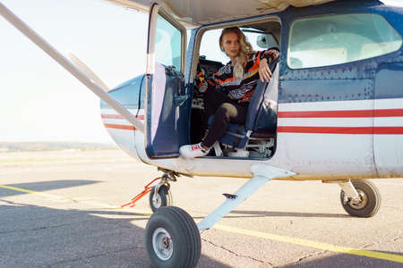Young fashionable woman pilot ready to fly, start training, in small airplane. Learning process.