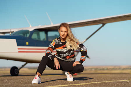 Young woman model with a modern haircut and fashionable sunglasses posing near a red plane wearing trendy casual outfit Archivio Fotografico