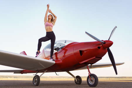 Athletic woman practicing stretching near a red private plane. Working out on the aerodrome on planes and sky background.