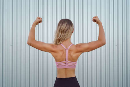 Close up of woman back with flexing her muscles while working out. Female bodybuilder with perfect biceps Archivio Fotografico