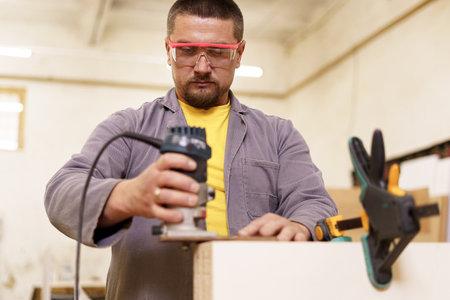 Carpenter Using Electric Sander in the workshop