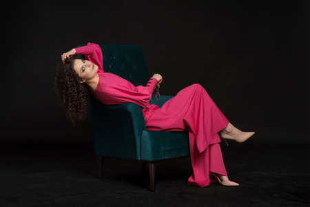 Fashionable women in bright pink costume sitting in a blue armchair on black background 스톡 콘텐츠