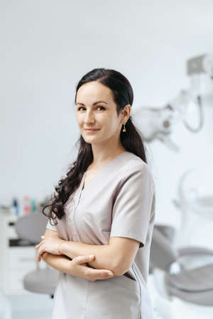 Portrait of female dentist smiling with arms crossed in dental clinic