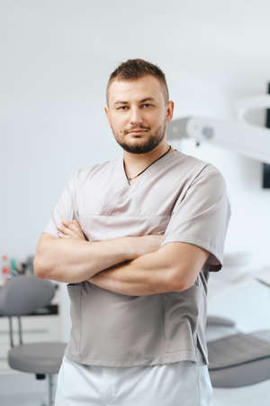 Portrait of man dentist smiling with arms crossed in dental clinic