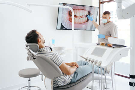 Dentist discussing with laying patient showing the image of his teeth on the screen
