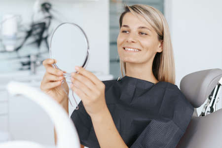 Young woman patient is looking in the mirror and admires her new smile after dental treatment in the dentistry clinic. 스톡 콘텐츠
