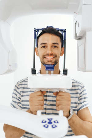 Young man doing computer 3d tomography of teeth and jaw in modern dental clinic