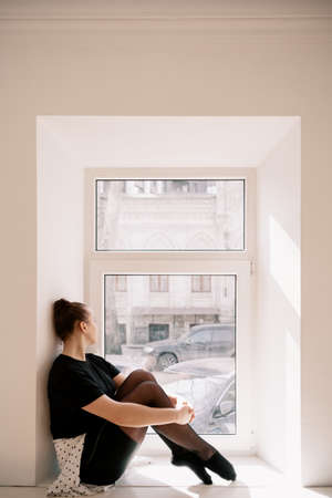 Cute teenager sitting near the window. Looking through the window, thinking 스톡 콘텐츠