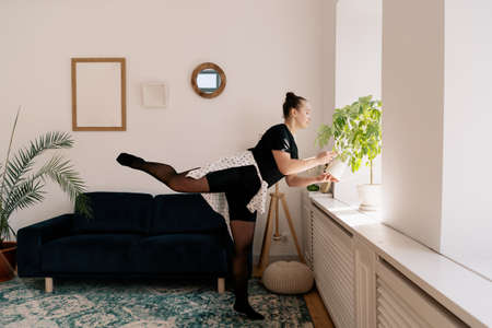 Teenager girl practicing at home while watering green potted plant on the window. Woman dancing indoors