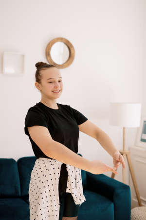 Teenager girl practicing ballet online classes at home. Woman dancing indoors