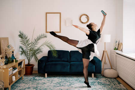 Young woman making a selfie while dancing at home. Ballerina at home 스톡 콘텐츠