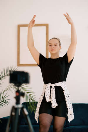 Online ballet classes, teacher explaining motion on camera screen. Young woman teaching ballet using a camera and tripod. 스톡 콘텐츠