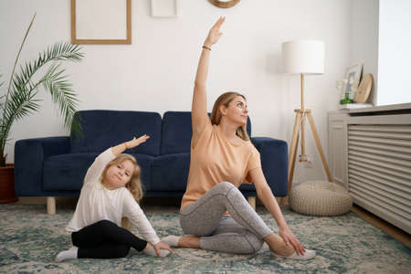 Young mother with little daughter practicing yoga at home. Family fizical activity, sporty mom and kid 스톡 콘텐츠