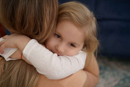Beautiful young woman and her charming little daughter are hugging and smiling at home