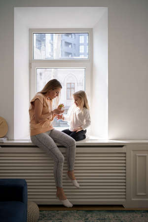Daughter who loves her mother give her a potted plant present while sitting on the window at home