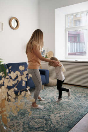 Carefree funny caucasian family young mom having fun with cute little kid girl jump dancing in living room, happy mother with small child daughter laugh do morning exercise together at home 스톡 콘텐츠