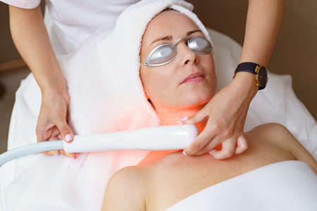 View of doctor cosmetologist doing anti aging procedure in cosmetology office. Satisfied woman in disposable hat lying on couch and relaxing. Working with Apparatus. Stock fotó