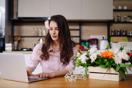 Young brunette woman with long wavy hair working on laptop with flowers on the desk with kitchen in background. Talented florist developing online sales getting ready for workshop.