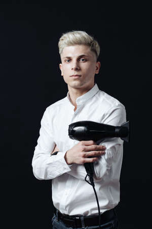Portrait of stylish professional hairdresser with blond hair. Man wearing white shirt, looking aside and holding a blow dryer near his face