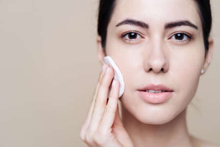 Beautiful Caucasian woman gently cleaning face with makeup remover pad on beige background with copy space Stock fotó