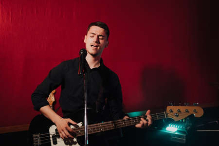 Talented handsome young guitarist man singing a song in studio recording on red background surrounded by instruments. Passion, hobby, singer, electric guitar