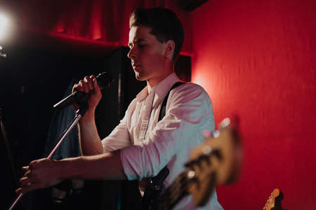 Talented handsome young guitarist man singing a song in studio recording on red background surrounded by instruments. Passion, hobby, singer, electric guitar Archivio Fotografico