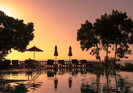 Beautiful sunset on tropical island Koh Phangan in Thailand. with sunbed trees in front Standard-Bild